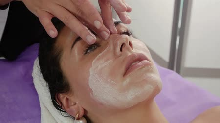 masszőr : Applying cream on the face of a beautiful girl. Face massage in spa beauty salon close-up. Beauty treatments for a young woman. Skin Care, Wellness, Beauty Care Concept Slow Motion
