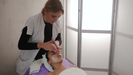 masszőr : Face massage in spa beauty salon close-up. Applying cream on the face of a beautiful girl. Skin Care, Wellness, Beauty Care Concept Slow Motion. Beauty treatments for a young woman