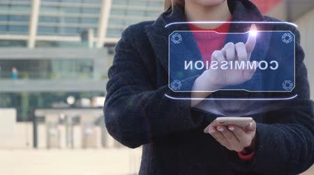 bizottság : Unrecognizable woman interacts HUD hologram with text Commission. Girl in the coat uses the technology of the future mobile screen on the background of the city