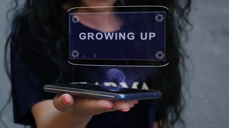 implementation : Unrecognizable curly brunette woman showing HUD hologram with text Growing UP. Girl uses technology of the future on a mobile screen