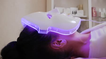 лицевой : Modern technologies of beauty and health. LED light anti-aging mask for facial skin care in a spa slow motion. A woman lies on a couch in a special mask
