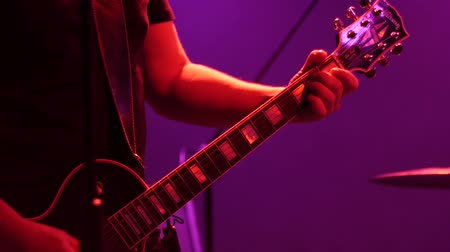 string instrument : Playing the guitar in multi-colored club lights. Close-up of hands playing an electric guitar.