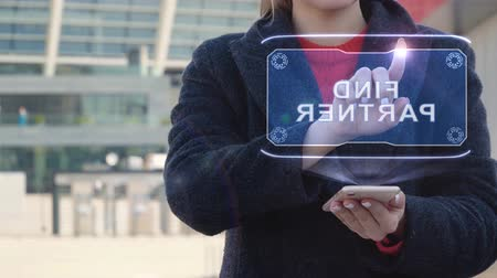 candidato : Unrecognizable woman interacts HUD hologram with text Find Partner. Girl in the coat uses the technology of the future mobile screen on the background of the city