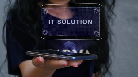 entellektüel : Unrecognizable curly brunette woman showing HUD hologram with text IT solution. Girl uses technology of the future on a mobile screen Stok Video