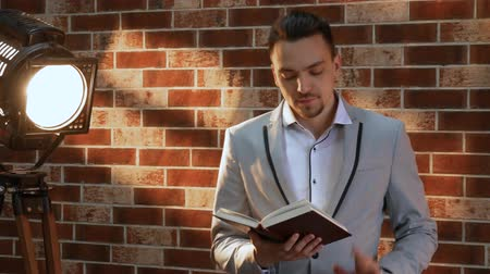 оценка : Man with a book in the loft style. Stylish man reads a book against a brick wall illuminated by a spotlight. Businessman in a jacket. The concept of knowledge