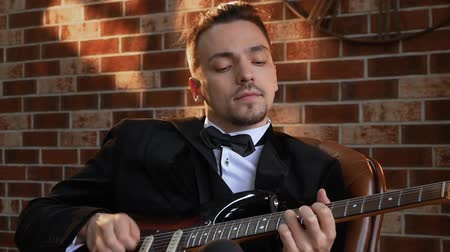 fama : Man with a beard plays on the electric guitar slow motion against a brick wall background. The musician picks the strings on the fretboard of the guitar to play chords and solos. Hobbies businessman Stock Footage