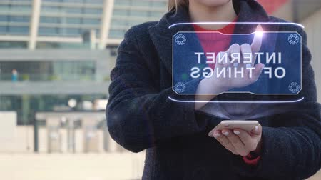 kaše : Unrecognizable woman interacts HUD hologram with text Internet of things. Girl in the coat uses the technology of the future mobile screen on the background of the city