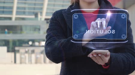 intelectual : Unrecognizable woman interacts HUD hologram with text IT solution. Girl in the coat uses the technology of the future mobile screen on the background of the city