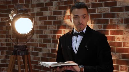 avaliação : Man with a book in the loft style. Stylish man speaks in a frame and holds a book against a brick wall illuminated by a spotlight. Businessman TV presenter in a jacket slams a book Vídeos
