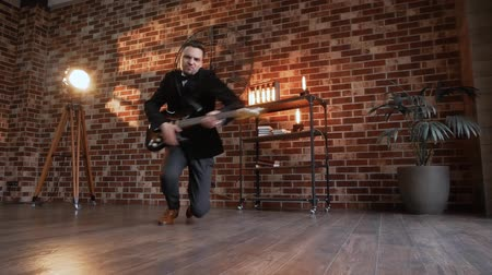 un : Man with beard playing on the electric guitar and falls to his knees slow motion against retro brick wall background with backlight. Musician showman glides on the floor