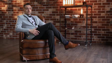 публиковать : Smiling man in a chair looks into the distance slow motion. The guy on the background of a brick wall in the style of a loft and shelves with books. Businessman in a jacket with a wrist watch thinks