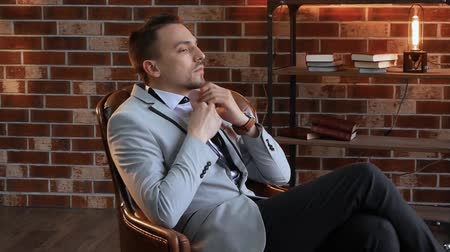 публиковать : Stylish man in a chair unzips his shirt in slow motion. The guy on the background of a brick wall in the style of a loft and shelves with books. Businessman in a jacket with a wrist watch leaves Стоковые видеозаписи