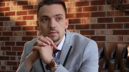 умный : Businessman in a jacket with a wrist watch thinks. Stylish man in a chair looks into the distance slow motion. The guy on the background of a brick wall in the style of a loft