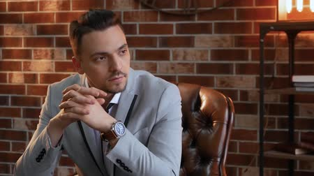 публиковать : Stylish man in a chair looks into the distance slow motion. The guy on the background of a brick wall in the style of a loft and shelves with books. Businessman in a jacket with a wrist watch thinks