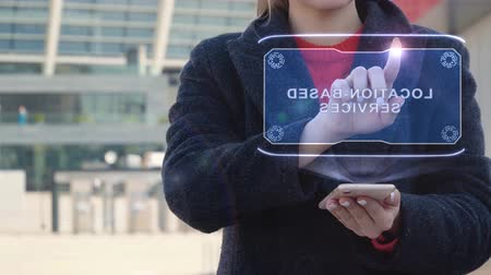 близость : Unrecognizable woman interacts HUD hologram with text Location-based services. Girl in the coat uses the technology of the future mobile screen on the background of the city
