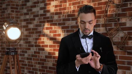 публиковать : Man looks at mobile phone. Slow motion. Guy with phone is preparing against the background of a brick wall in the loft style. Businessman in a jacket with a bow tie smile Стоковые видеозаписи