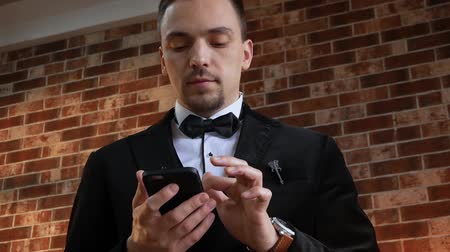 публиковать : Businessman hold smartphone in a jacket with a bow tie. Man looks at mobile phone. Slow motion. Guy with phone against the background of a brick wall in the loft style. Low angle