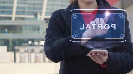 foro : Unrecognizable woman interacts HUD hologram with text Portal. Girl in the coat uses the technology of the future mobile screen on the background of the city