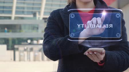 信頼性 : Unrecognizable woman interacts HUD hologram with text Reliability. Girl in the coat uses the technology of the future mobile screen on the background of the city 動画素材