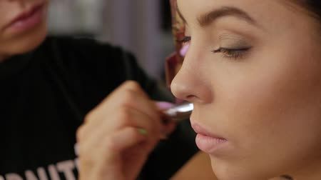 contornos : Hand of a professional make-up artist tones the face of a beautiful girl with a brush. Close-up of a cheek in a beauty salon. Woman client in a beauty salon does makeup