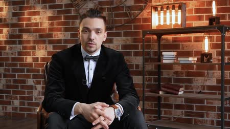 értékelés : TV presenter is telling while sitting in armchair. Stylish man talking in frame against a brick wall, illuminated by floodlight in the loft style and shelves with books. Blogger businessman in jacket Stock mozgókép