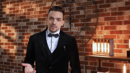 публиковать : Man blogger is telling something. Stylish man talking in a frame against a brick wall, illuminated by a floodlight in the loft style. TV presenter businessman in a jacket Стоковые видеозаписи