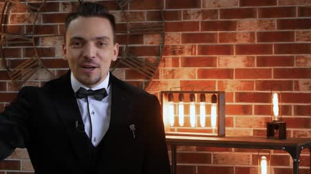 değerlendirme : Stylish man talking in a frame against a brick wall, illuminated by a floodlight in the loft style. TV presenter businessman in a jacket. Man blogger is telling something Stok Video
