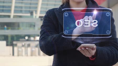 estratégico : Unrecognizable woman interacts HUD hologram with text SEO. Girl in the coat uses the technology of the future mobile screen on the background of the city Vídeos