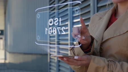 iso : Unrecognizable businesswoman interacts HUD hologram with text ISO 27001. Woman in the coat uses the technology of the future mobile screen on the background of the city Stock Footage