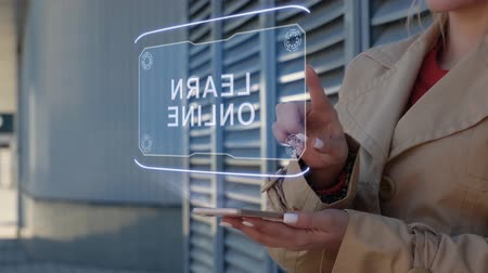 dicionário : Unrecognizable businesswoman interacts HUD hologram with text Learn Online. Woman in the coat uses the technology of the future mobile screen on the background of the city