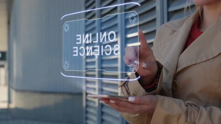 k nepoznání osoba : Unrecognizable businesswoman interacts HUD hologram with text Online science. Woman in the coat uses the technology of the future mobile screen on the background of the city