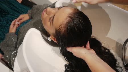 szampon : Hairdresser applies the product or shampoo to womens hair in a beauty salon. Slow motion of a beautiful young woman takes care of hair health, beauty treatments, woman in a spa beauty salon. Wideo