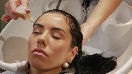 szampon : Hand applies the product or shampoo to womens hair in a beauty salon. Slow motion of a beautiful young woman takes care of hair health, beauty treatments, woman in a spa beauty salon.