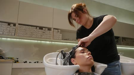 szampon : Hairdresser massages female hair in a beauty salon. Beautiful young woman cares for hair health, cosmetic procedures shampoo, woman in spa beauty salon. Wash female hair