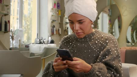 várjon : Smiling lady takes care of her hair and solves problems using a smartphone. Beautiful happy woman with a towel on her head and a mobile phone is waiting for hair treatment in a beauty salon