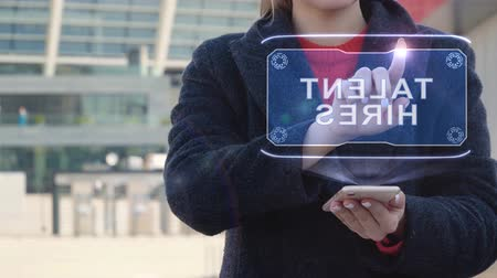 талант : Unrecognizable woman interacts HUD hologram with text Talent hires. Girl in the coat uses the technology of the future mobile screen on the background of the city