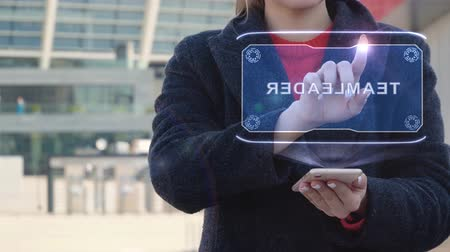 übersetzen : Unrecognizable woman interacts HUD hologram with text Teamleader. Girl in the coat uses the technology of the future mobile screen on the background of the city