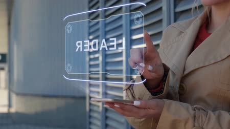 promover : Unrecognizable businesswoman interacts HUD hologram with text Leader. Woman in the coat uses the technology of the future mobile screen on the background of the city