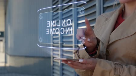 зарабатывать : Unrecognizable businesswoman interacts HUD hologram with text Online income. Woman in the coat uses the technology of the future mobile screen on the background of the city Стоковые видеозаписи
