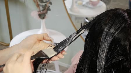 saç kremi : Brunette in the salon treats hair at a professional hairdresser. Stylists hands applying a professional mask for hair care with a brush are covered with a moisturizing mask