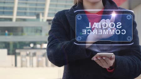 implementation : Unrecognizable woman interacts HUD hologram with text Social commerce. Girl in the coat uses the technology of the future mobile screen on the background of the city Stock Footage