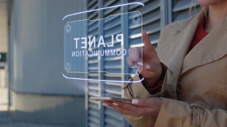 automatyka : Unrecognizable businesswoman interacts HUD hologram with text Planet communication. Woman in the coat uses the technology of the future mobile screen on the background of the city Wideo
