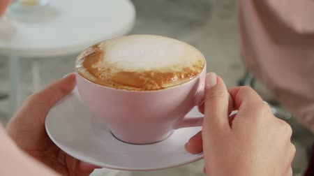 kahve molası : Female hands hold hot coffee with tasty foam. Cup of cappuccino on a saucer close up