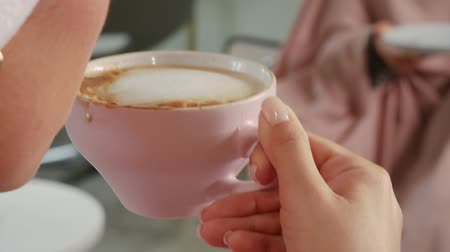 pauza : A woman in a towel on her head drinks hot coffee while holding a cup and saucer in her hands. Female lips take a sip of coffee foam. Frame with copy space at the end