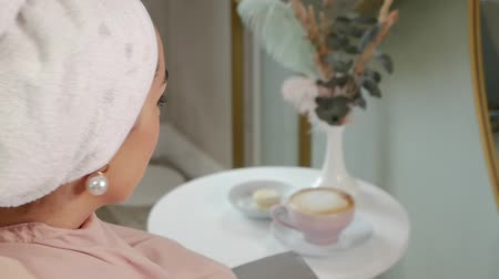 kahve molası : Pretty woman in a towel on her head looks at a cup of hot coffee on a table. Lady is waiting for hair treatment in a beauty salon