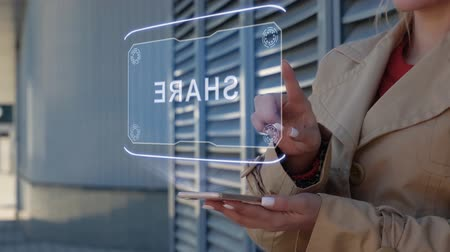 dávat : Unrecognizable businesswoman interacts HUD hologram with text Share. Woman in the coat uses the technology of the future mobile screen on the background of the city