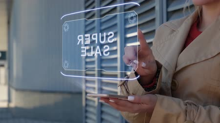 rachunkowość : Unrecognizable businesswoman interacts HUD hologram with text Super sale. Woman in the coat uses the technology of the future mobile screen on the background of the city Wideo