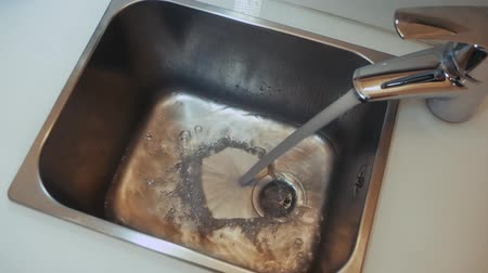 носик : Water flows from the faucet to the sink top view. Waterfow streaming in metal sink. Liquid stream going down the drain slow motion