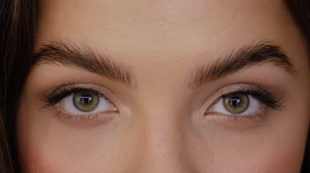 umutlu : Beautiful girl with green brown eyes after Eyebrow Lamination Procedure close-up. Young woman looks straight into the frame and closes her eyes and smiling slow motion