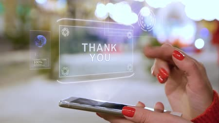 obrigado : Female hands interact with HUD hologram text Thank you. Woman with red nails and sweater uses the holographic technology of the future in the smartphone screen on the background of street